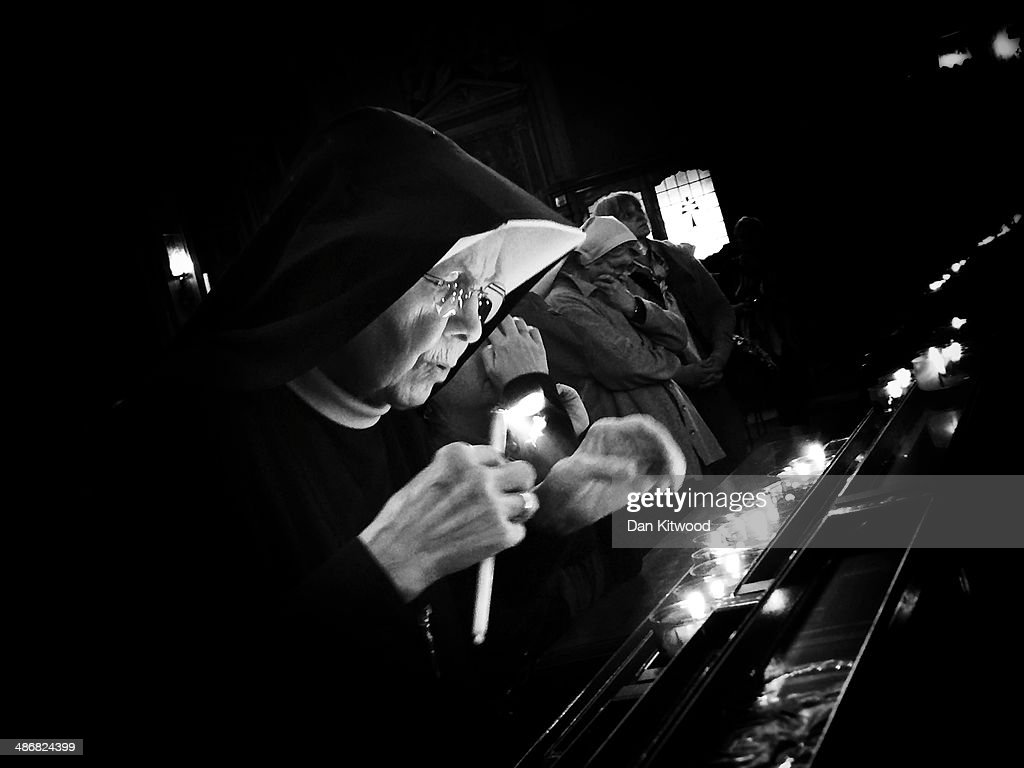 A nun arranges candles at the Polish Church Santo Spirito in Sassia Sanctuary of Divine Mercy on April 26 2014 in Vatican City Vatican Dignitaries...