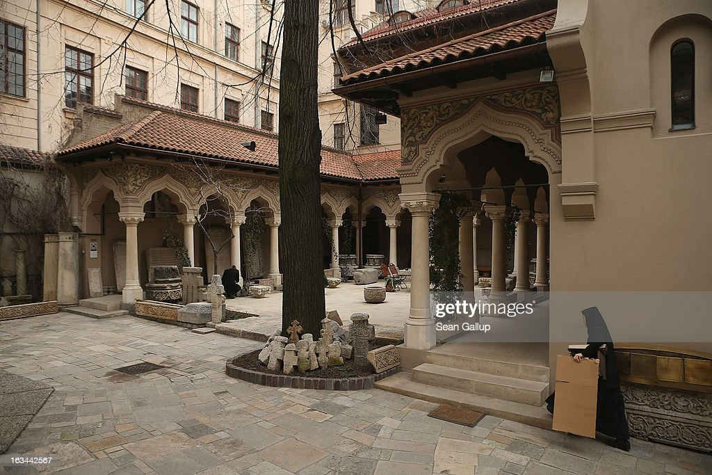 A nun carrying a piece of cardboard walks across the grounds of the Stavropoleos Monastery in the Lipscani old town quarter on March 8, 2013 in Bucharest, Romania. Both Romania and Bulgaria have been members of the European Union since 2007 and restrictions on their citizens' right to work within the EU are scheduled to end by the conclusion of this year. However, Germany's interior minister announced recently that he would veto the two countries' entry into the Schengen Agreement, which would not affect labour rights but would prevent passport-free travel.
