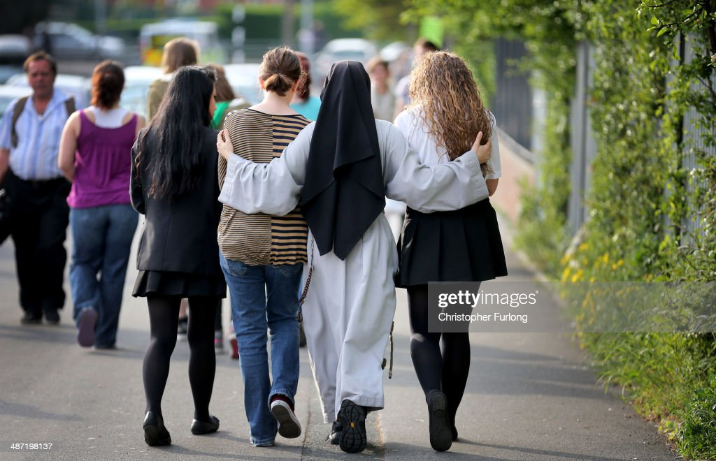 A nun comforts students outside Corpus Christi Catholic College in Neville Road, Leeds, where a female teacher was fatally stabbed earlier today on April 28, 2014 in Leeds, England. A fifteen year old male student has been arrested in connection with the stabbing of the teacher.
