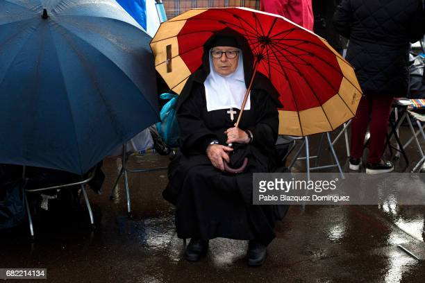 A nun covers from the rain with an umbrella as she waits for the arrival of Pope Francis in the Sanctuary of Fatima on May 12 2017 in Fatima Portugal...