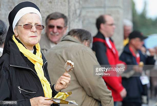 A nun eats ice cream while waiting for the arrival of Pope Benedict XVI at the Olympiastadion stadium where the Pope was expected to give a Catholic...