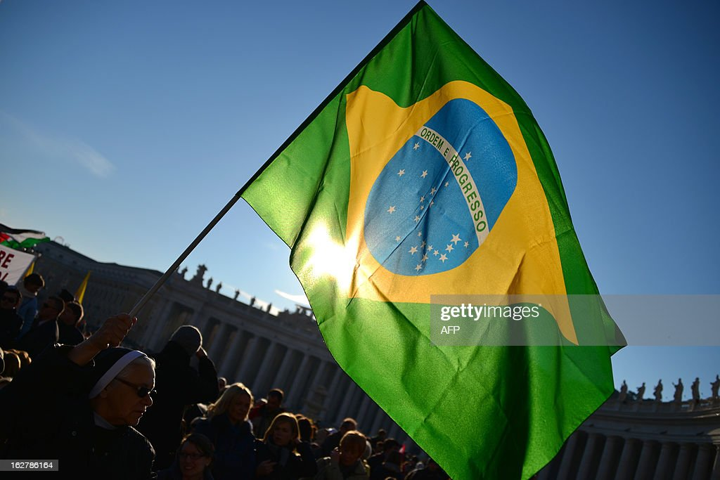 A nun holds a Brazilian flag on St Peter's square ahead of Pope Benedict XVI last weekly audience on February 27, 2013 at the Vatican. Pope Benedict XVI will hold the last audience of his pontificate in St Peter's Square on Wednesday on the eve of his historic resignation as leader of the world's 1.2 billion Catholics. AFP PHOTO / GABRIEL BOUYS