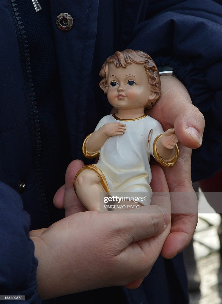 A nun holds a effigy of the infant Jesus to be blessed by Pope Benedict XVI during his weekly Angelus prayer on December 16, 2012 at the Vatican. The pontiff prayed for families of the victims in the Newtown, Connecticut, school massacre in the United States during his traditional weekly address to pilgrims on St Peter's Square. AFP PHOTO / VINCENZO PINTO