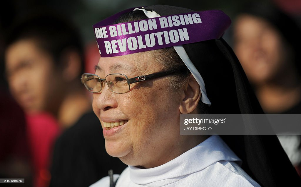 A nun joins other Filipinos as they take part in a gathering to mark the 'One Billion Rising' campaign in Manila on February 14, 2016. The campaign aims to end violence against women and children. AFP PHOTO / Jay DIRECTO / AFP / JAY DIRECTO