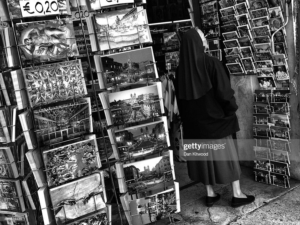A Nun looks at items in a souvenir shop on April 25, 2014 in Vatican City, Vatican. Dignitaries, heads of state and Royals, from Europe and across the World, are gathering in the Vatican ahead of tomorrow's canonisations. The late Pope John Paul II and Pope John XXIII will be canonised on Sunday 27 April, inside the Vatican when 800,000 pilgrims from around the world are expected to attend.