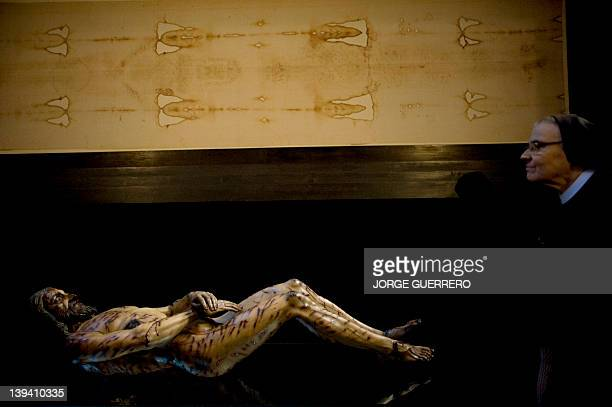 A nun observes a image of Christ next to a facsimile of 'The Shroud of Turin' at the Cathedral of Malaga on February 20 2012 AFP PHOTO/ JORGE GUERRERO