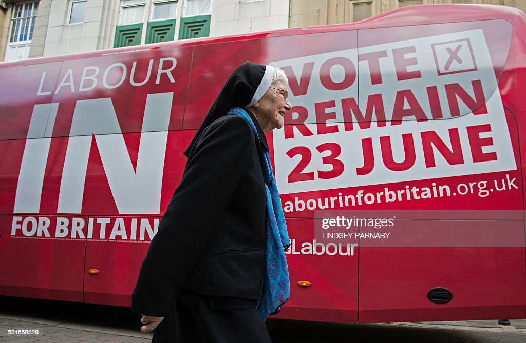 A nun passes the Labour Party 'battle-bus' as Britain's opposition Labour Party, Jeremy Corybn (unseen), arrives to deliver a speech on the merits of Britain remaining in the European Union (EU), in Doncaster on May 27, 2016. With just under four weeks to go until the June 23 referendum, the Remain camp is on 53 percent and the Leave campaign on 47 percent, according to the What UK Thinks website's average of the most recent six opinion polls. / AFP / Lindsey Parnaby