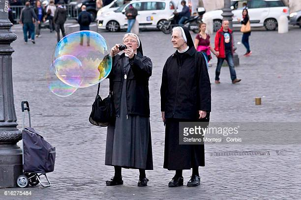Nun photographing soap bubbles in Piazza del Popolo on October 20 2016 in Rome Italy