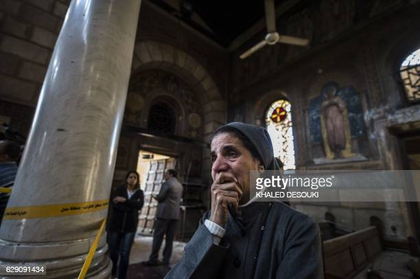 A nun reacts as Egyptian security forces inspect the scene of a bomb explosion at the Saint Peter and Saint Paul Coptic Orthodox Church on December...