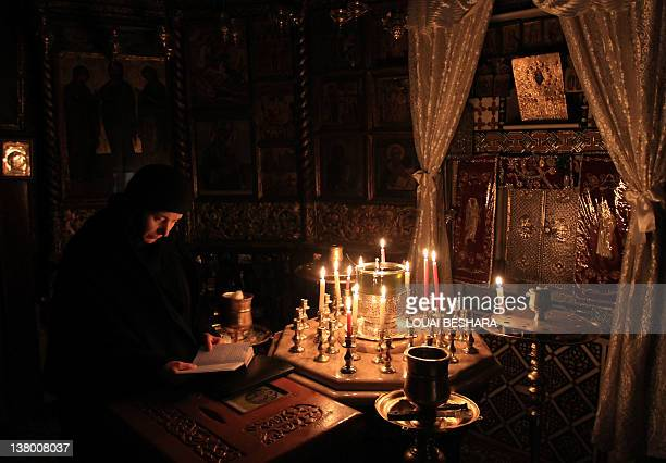 A nun reads in a chapel at the Sednaya Monastery as journalists are given a guided government tour to view damage caused to the convent during a...
