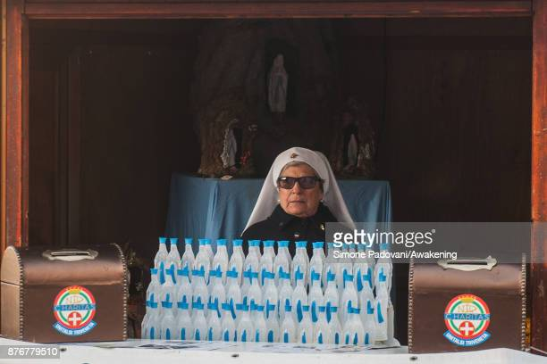 Nun sells holy water in Virgin Mary's shaped bottles on November 20 2017 in Venice Italy The Festa della Salute is the least 'touristy' of the...