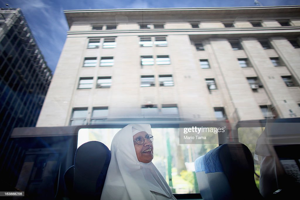 A nun sits in a bus with the city reflected in a window following Sunday Mass honoring Pope Francis outside the Metropolitan Cathedral on March 17, 2013 in Buenos Aires, Argentina. Francis was the archbishop of Buenos Aires and is the first Pope to hail from South America.