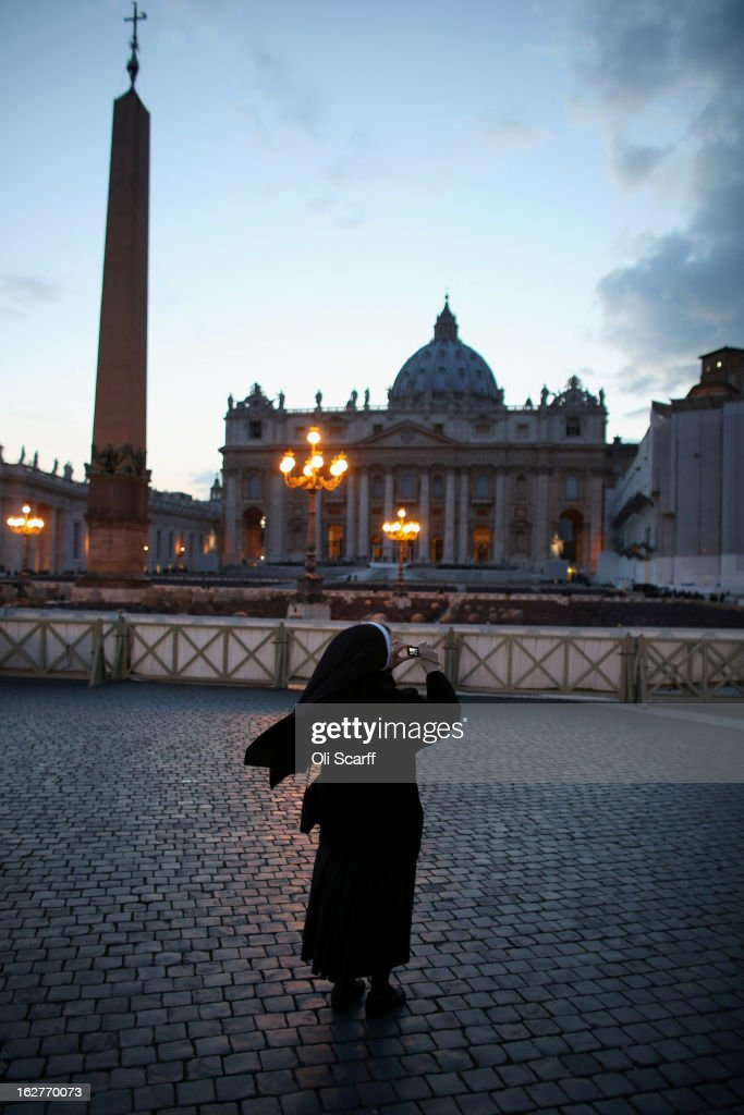 A nun takes a photograph as the sun sets behind St Peter's Basilica on February 26, 2013 in Vatican City, Vatican. The Pontiff will hold his last weekly public audience on February 27, 2013 before he retires the following day. Pope Benedict XVI has been the leader of the Catholic Church for eight years and is the first Pope to retire since 1415. He cites ailing health as his reason for retirement and will spend the rest of his life in solitude away from public engagements.