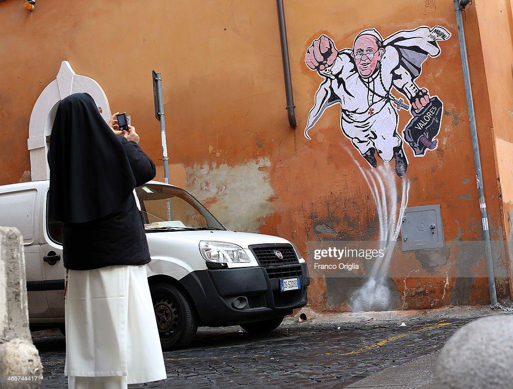 A nun takes a picture with her smartphone of a graffiti featuring a 'superhero' version of Pope Francis appears in Borgo Pio, next to St. Peter's Square on January 29, 2014 in Rome, Italy. The image has started circulating from the twitter account of the Vatican and has rapidly spread around the world.
