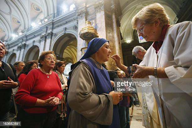 A nun takes Communion in the Metropolitan Cathedral during Mass on the day after Pope Francis formerly Cardinal Jorge Mario Bergoglio was elected at...