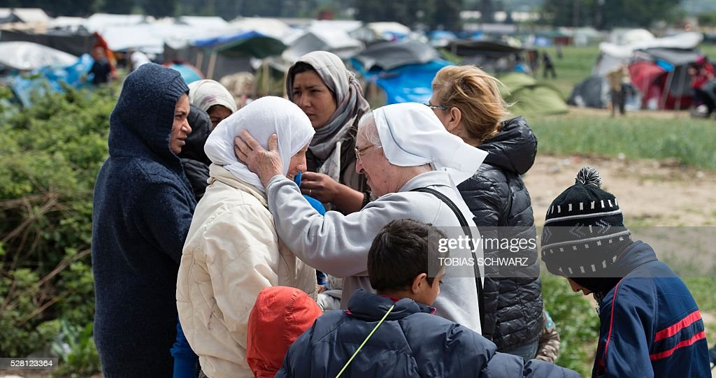 A nun talks to a woman at a makeshift camp for migrants and refugees near the village of Idomeni not far from the Greek-Macedonian border on May 4, 2016. Some 54,000 people, many of them fleeing the war in Syria, have been stranded on Greek territory since the closure of the migrant route through the Balkans in February. / AFP / TOBIAS