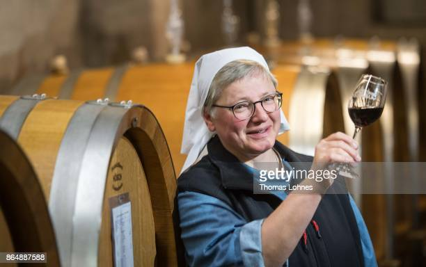 Nun Thekla of St Hildegard Abbey looks to a Spaetburgunder red wine in the cellar on October 20 2017 near Rudesheim on the Rhine Germany The St...