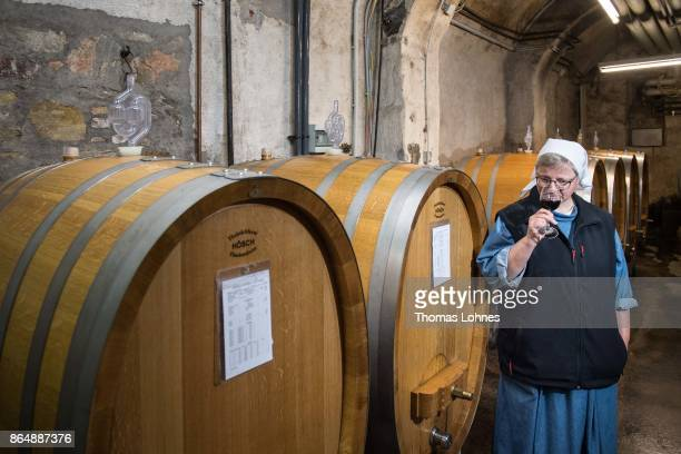 Nun Thekla of St Hildegard Abbey smells a Spaetburgunder red wine in the cellar on October 20 2017 near Rudesheim on the Rhine Germany The St...