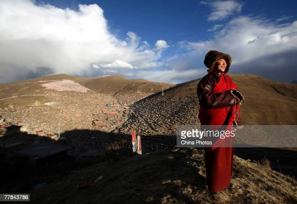 A nun views scenery on a hill at the Serthar Wuming Buddhist Study Institute on November 9 2007 in the Tibetan autonomous region of China The Wuming...