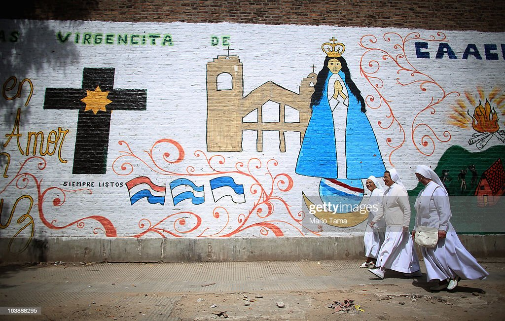Nun walk past a mural near the Virgin of the Miracles of Caacupe church following Sunday Mass in the Villa 21-24 slum, where archbishop Jorge Mario Bergoglio, now Pope Francis, used to perform charity work, on March 17, 2013 in Buenos Aires, Argentina. Francis was the archbishop of Buenos Aires and is the first Pope to hail from South America. Some locals are now affectionately calling Francis, known for his charity work in the slums, the 'slum pope.'