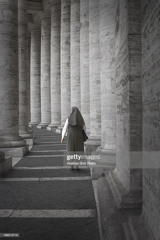 Nun walking away down St Peter's Colonnade in Rome