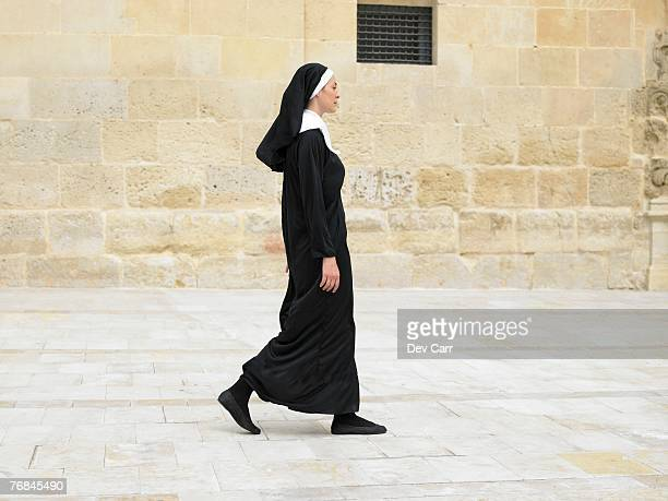 Nun walking in front of stone wall, Alicante, Spain,