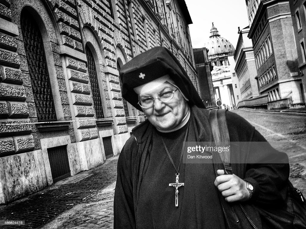A nun walks down an alleyway on April 26, 2014 in Vatican City, Vatican. Dignitaries, heads of state and Royals, from Europe and across the World, are gathering in the Vatican ahead of tomorrow's canonisations. The late Pope John Paul II and Pope John XXIII will be canonised on Sunday 27 April, inside the Vatican when 800,000 pilgrims from around the world are expected to attend.