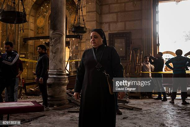 A nun walks through the site of the bombing on December 11 2016 in Cairo Egypt A bomb exploded inside the Saint Mark's Coptic Orthodox Cathedral of...