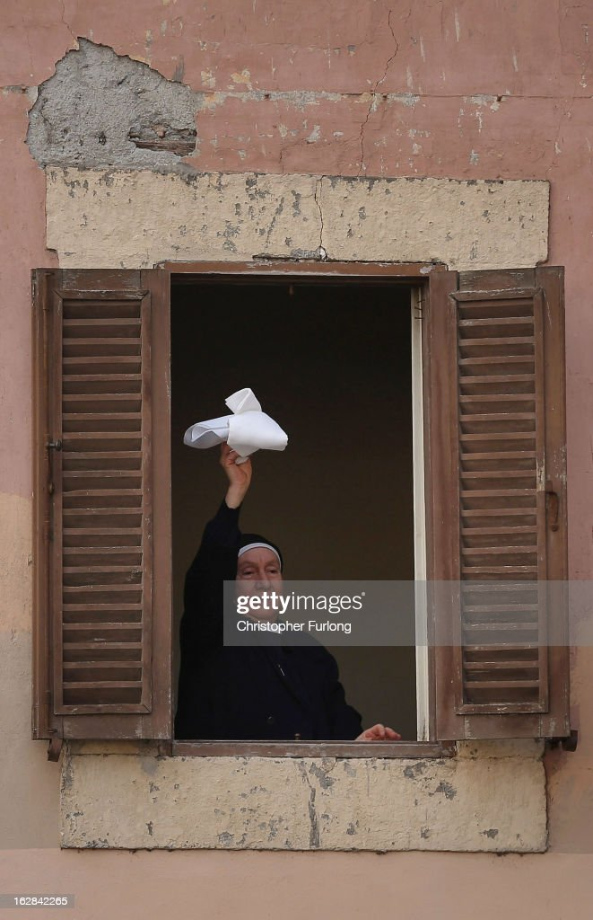 A nun waves her handkerchief as she waits for Pope Benedict XVI to address pilgrims, for the last time as head of the Catholic Church, from the window of Castel Gandolfo where he will start his retirement today on February 28, 2013 in Rome, Italy. Pope Benedict XVI has been the leader of the Catholic Church for eight years and is the first Pope to retire since 1415. He will stay at the Papal Summer residence of Castel Gandolfo until renovations are complete at a monastery in the grounds of the Vatican and will be known as Roman Pope Emeritus. Alternate crop of #162841985