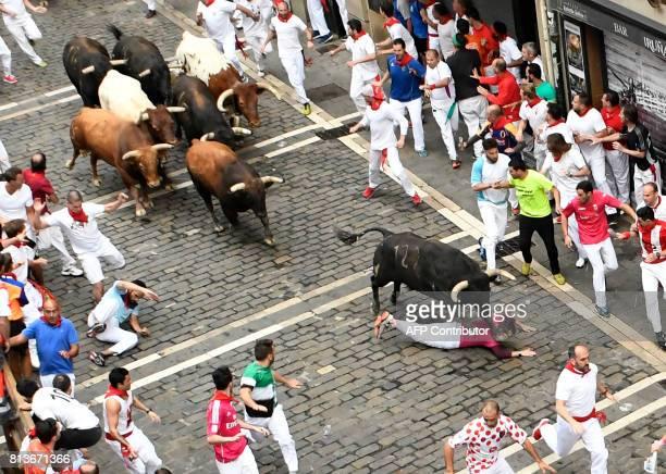 A Nunez del Cuvillo's fighting bull runs overa fallen participant during the seventh bull run of the San Fermin festival in Pamplona northern Spain...