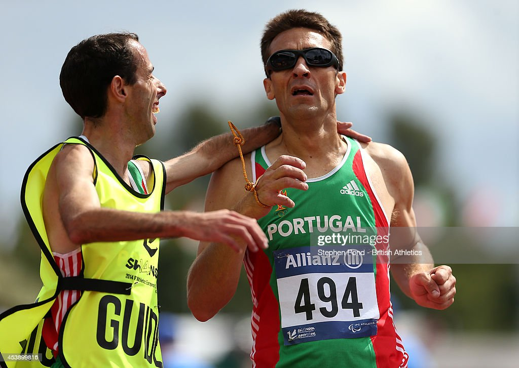 Nuno Alves (R) and his guide Ricardo Abreu of Portugal finish first in the Men's 5000m T11 event during day three of the IPC Athletics European Championships at Swansea University Sports Village on August 21, 2014 in Swansea, Wales.