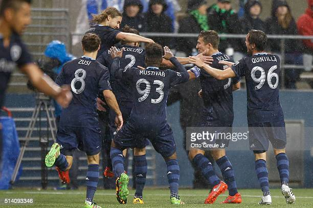 Nuno Coelho of Sporting Kansas City is congratulated by teammates after scoring a goal against the Seattle Sounders FC at CenturyLink Field on March...