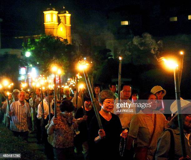 Nuns and Catholics hold bamboo torches during the peace march from the Urakami Cathedral toward the Peace Memorial park in Nagasaki on the southern...
