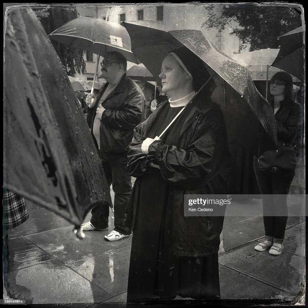 Nuns and Parishioners attend church services in the rain at Wawel Cathedral in Krakow Poland celebrating The Feast of Corpus Christi or the Feast of...