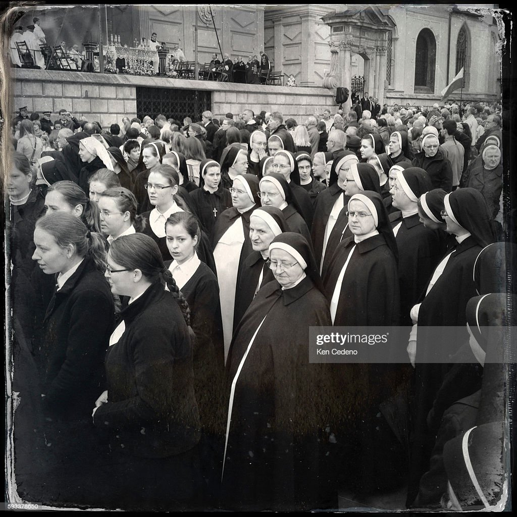 Nuns and Parishioners walk in the rain to attend church services at Wawel Cathedral in Krakow Poland celebrating The Feast of Corpus Christi or the...