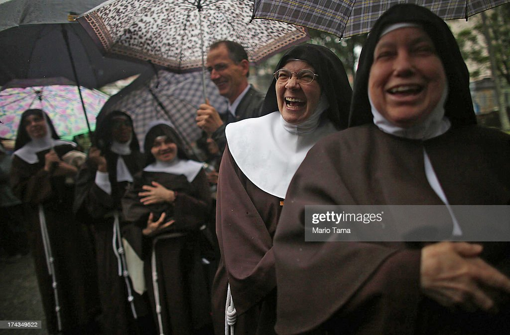 Nuns from the Nossa Senhora dos Anjos monastery wait in line in the rain to attend Pope Francis' visit to the Hospital de Sao Francisco de Assis (Hospital of Saint Francis of Assisi) on July 24, 2013 in Rio de Janeiro, Brazil. The nuns rarely leave the monastery. More than 1.5 million pilgrims are expected to join Pope Francis for his visit to the Catholic Church's World Youth Day celebrations. Pope Francis will deliver his welcome address to the celebrations on Copacabana Beach on July 25 as World Youth Day runs July 23-28.