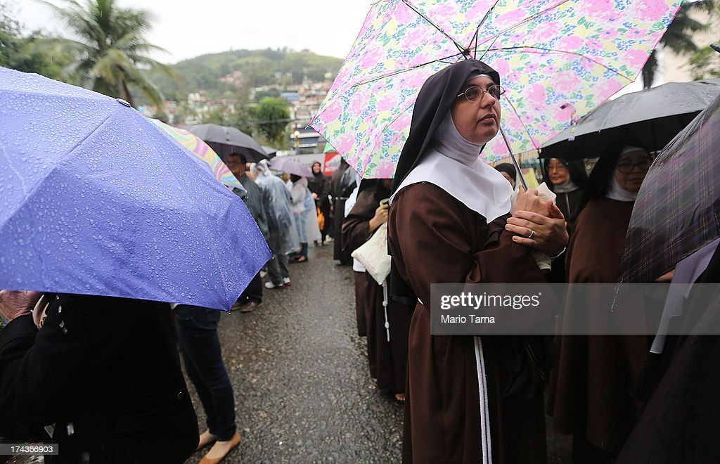 Nuns from the Nossa Senhora dos Anjos monastery (R) wait in line in the rain to attend Pope Francis' visit to the Hospital de Sao Francisco de Assis (Hospital of Saint Francis of Assisi) on July 24, 2013 in Rio de Janeiro, Brazil. The nuns rarely leave the monastery. More than 1.5 million pilgrims are expected to join Pope Francis for his visit to the Catholic Church's World Youth Day celebrations. Pope Francis will deliver his welcome address to the celebrations on Copacabana Beach on July 25 as World Youth Day runs July 23-28.