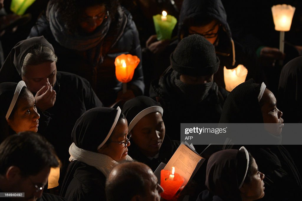 Nuns hold candles during the celebration of the Way of the Cross on Good Friday on March 29, 2013 at the Colosseum in Rome. Pope Francis presided over his first Good Friday which will culminate in a torch-lit procession at Rome's Colosseum and prayers for peace in a Middle East 'torn apart by injustice and conflicts'. AFP PHOTO / GABRIEL BOUYS