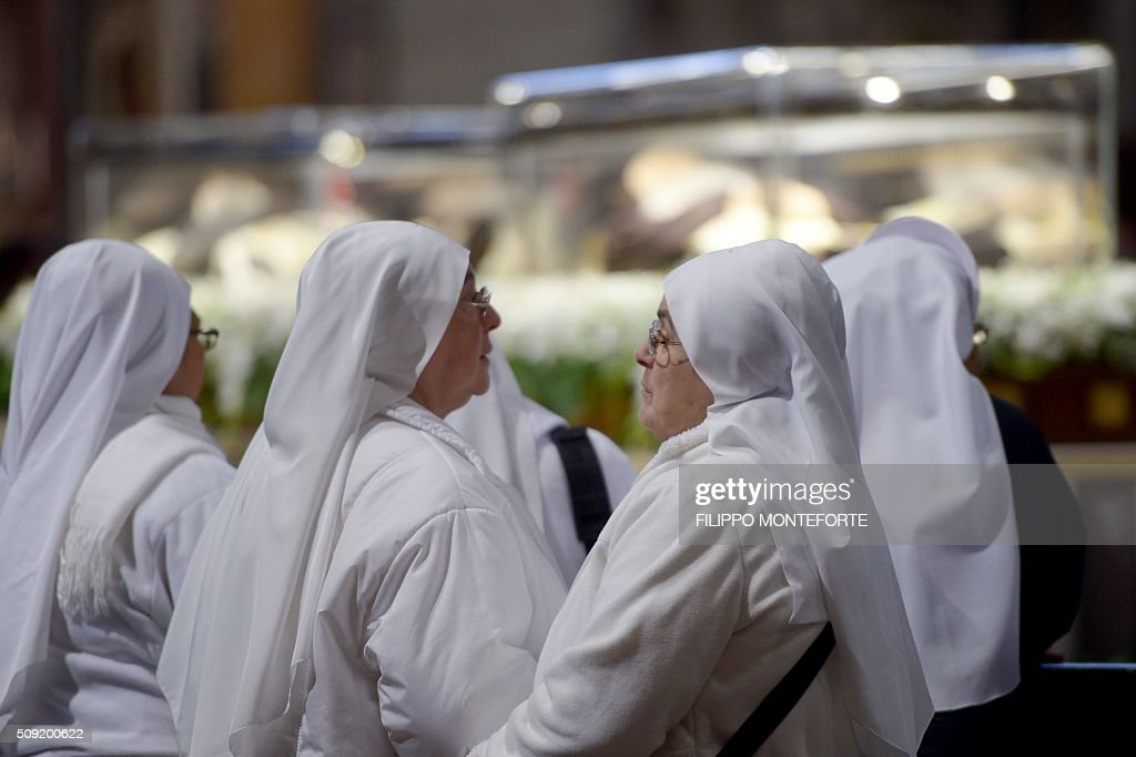 Nuns look stand near the embalmed corpses of two Catholic saints, Italian friar Padre Pio and Leopold Mandic on February 9, 2016 at St Peter's basilica in Vatican where the saints are on display until February 11. Pio was revered during his lifetime (1887-1968) and his popularity has continued to grow since his death, particularly in Italy, where mini-statues and pictures of the mystical Capuchin friar are ubiquitous. / AFP / FILIPPO MONTEFORTE