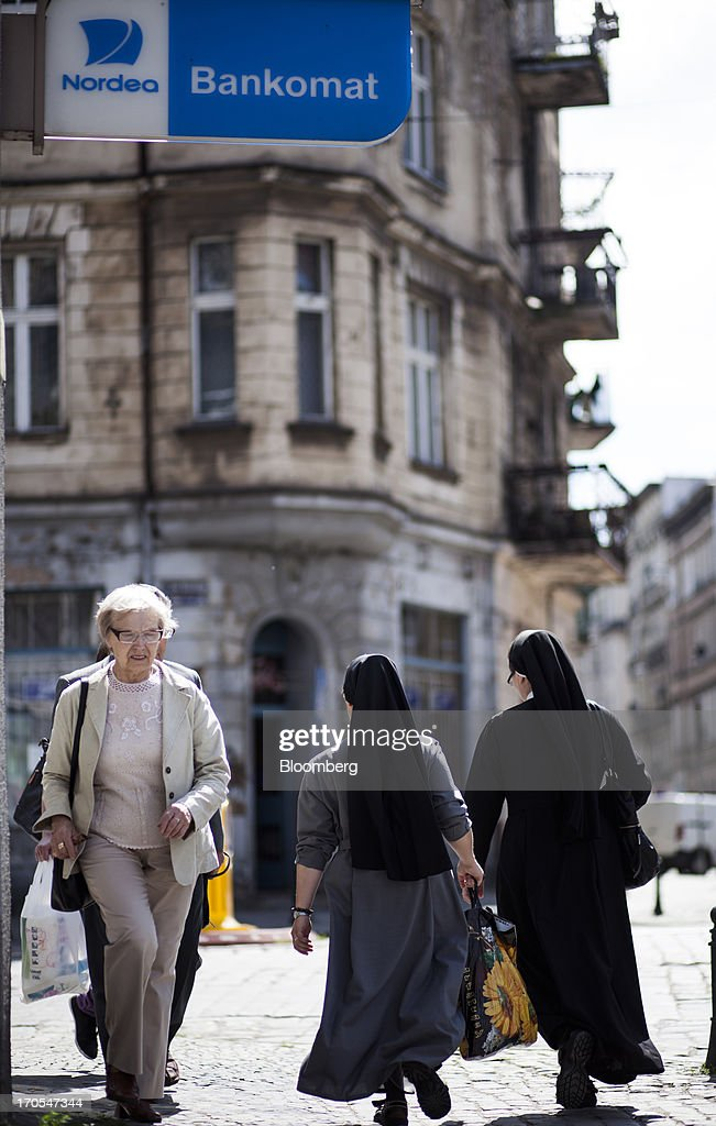 Nuns pass a Nordea Bank Polska SA bank branch in Wroclaw, Poland, on Friday, June 14, 2013. PKO Bank Polski SA, Poland's biggest lender, surged to a five-month high after signing an agreement to buy Nordea Bank AB's Polish assets to increase its dominance on the European Union's largest eastern market. Photographer: Bartek Sadowski/Bloomberg via Getty Images