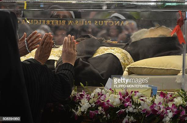 Nuns pray in front of the exhumed body of mystic saint Padre Pio in the Catholic church of San Lorenzo fuori le Mura in Rome on February 4 2016 The...