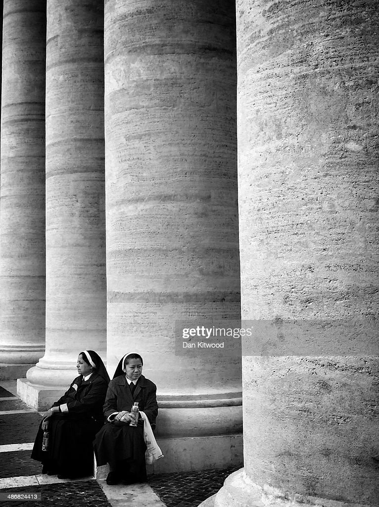 Nuns relax underneath the Colonnade in St Peter's Square on April 26, 2014 in Vatican City, Vatican. Dignitaries, heads of state and Royals, from Europe and across the World, are gathering in the Vatican ahead of tomorrow's canonisations. The late Pope John Paul II and Pope John XXIII will be canonised on Sunday 27 April, inside the Vatican when 800,000 pilgrims from around the world are expected to attend.