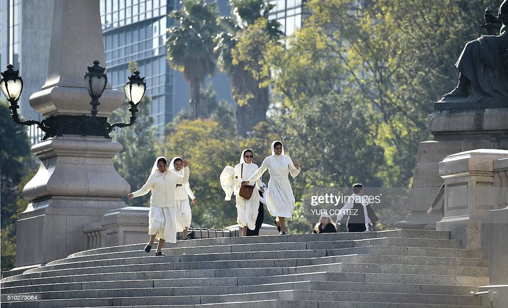Nuns run to see Pope Francis as he passes by the Angel of Independence square on February 14, 2016 in Mexico City. The pope urged Mexicans on Sunday to turn their country into a land of opportunity where there is no need to emigrate or mourn victims 'of the merchants of death.' AFP PHOTO/ Yuri CORTEZ / AFP / YURI CORTEZ