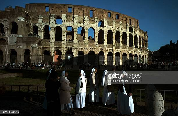 Nuns take pictures of the Colosseum at sunset on November 21 2014 in Rome AFP PHOTO / FILIPPO MONTEFORTE
