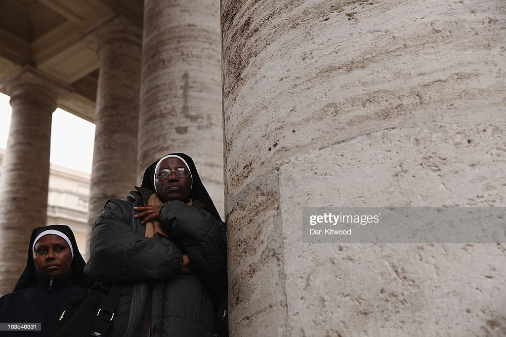Nuns wait under the colonnade as a rain storm passes over St Peter's Square on March 12, 2013 in Vatican City, Vatican. Pope Benedict XVI's successor is being chosen by the College of Cardinals in Conclave in the Sistine Chapel. The 115 cardinal-electors, meeting in strict secrecy, will need to reach a two-thirds-plus-one vote majority to elect the 266th Pontiff.