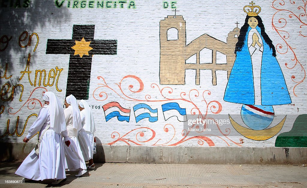 Nuns walk past a mural near the Virgin of the Miracles of Caacupe church following Sunday Mass in the Villa 21-24 slum, where archbishop Jorge Mario Bergoglio, now Pope Francis, used to perform charity work, on March 17, 2013 in Buenos Aires, Argentina. Francis was the archbishop of Buenos Aires and is the first Pope to hail from South America. Some locals are now affectionately calling Francis, known for his charity work in the slums, the 'slum pope.'