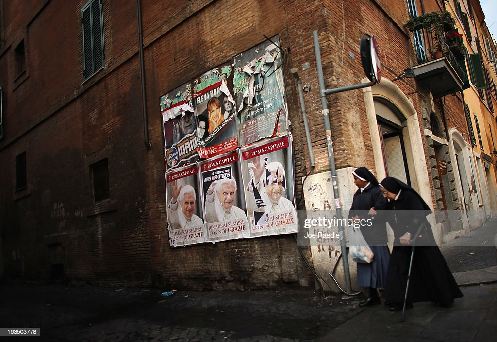 Nuns walk past a poster of Pope Benedict XVI hanging on a wall near Vatican City on March 11, 2013 in Rome, Italy. Cardinals are set to enter the conclave to elect a successor to Pope Benedict XVI after he became the first pope in 600 years to resign from the role. The conclave is scheduled to start on March 12 inside the Sistine Chapel and will be attended by 115 cardinals as they vote to select the 266th Pope of the Catholic Church.