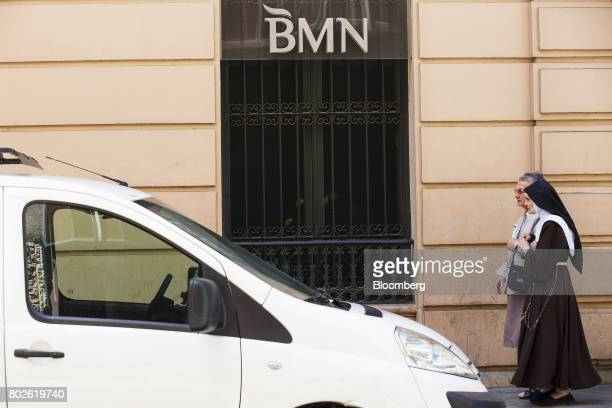 Nuns walk past the barred windows of a Banco Mare Nostrum SA bank branch in Madrid on Wednesday June 28 2017 Bankia SA agreed to acquire Banco Mare...