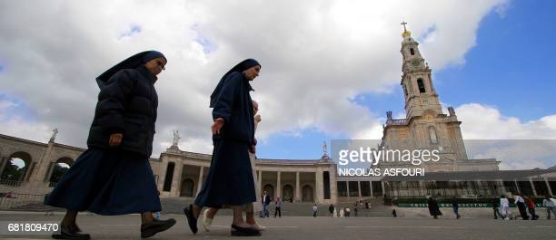 Nuns walk past the Fatima sanctuary as they discuss Pope John Paul II's condition in Fatima 01 April 2005 Pope John Paul II hovered close to death...