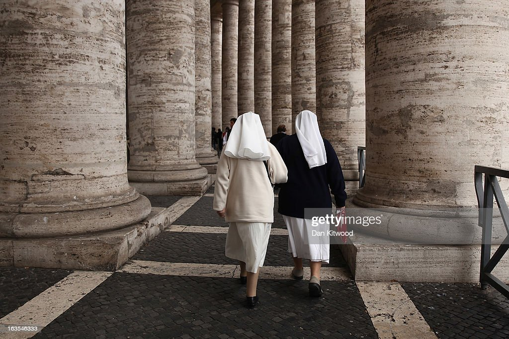 Nuns walk under the colonnade as a rain storm passes over St Peter's Square on March 12, 2013 in Vatican City, Vatican. Pope Benedict XVI's successor is being chosen by the College of Cardinals in Conclave in the Sistine Chapel. The 115 cardinal-electors, meeting in strict secrecy, will need to reach a two-thirds-plus-one vote majority to elect the 266th Pontiff.